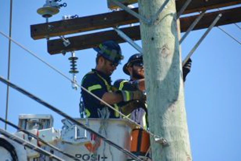 ['Jordan Bigelow, left, and Jeff Mahar, workers for City of Summerside electric department worked on a power lines after a single-vehicle accident knocked out power early Wednesday morning.']