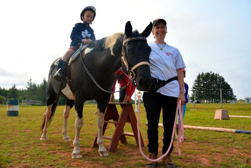 Caden MacGregor, from Summerside, climbs on the saddle while Celina Gallant steadies the horse with the reins.