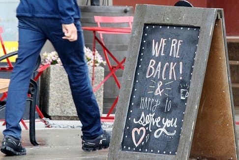 A sign in Kensington welcomes customers back to the Higher Ground coffee shop.
