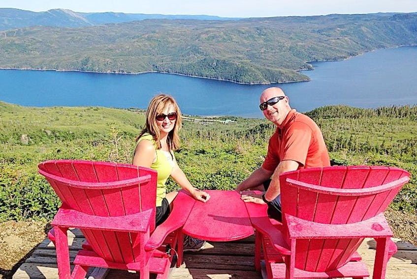 Lisa and Junior Pinksen pose for a photo on the red chairs from this spectacular view overlooking Bonne Bay in Gros Morne National Park.