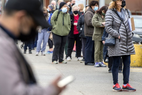 People line up outside of a Shoppers Drug Mart location on Toronto's Danforth Avenue for their COVID-19 vaccine, Thursday March 11, 2021.