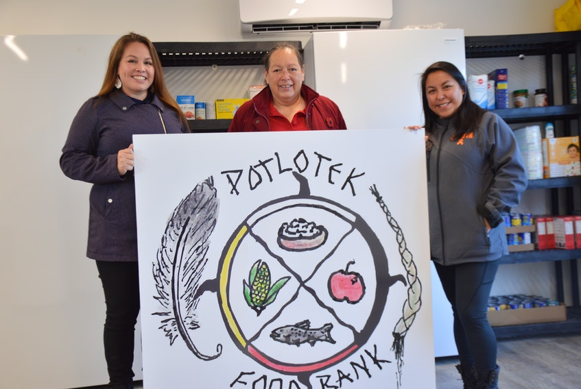 From left, Tahirih Paul, Anita Basque and Mary Susan Lafford hold up the food bank sign at the grand opening of the Potlotek facility on Wednesday. The sign was designed by local artist Mary Lee Johnson, whose work was chosen from 13 other submissions. OSCAR BAKER III • CAPE BRETON POST