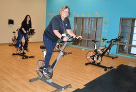 Anita Vosman-O'Rourke, right, director of member relations for the Frank Rudderham Family YMCA in Sydney, and Tanya Horne, manager of member and group fitness, take a turn in the expanded spin room. A wall was opened up to allow for social distancing between equipment. Sharon Montgomery-Dupe/Cape Breton Post