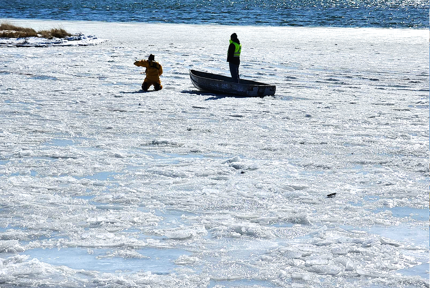 A member of a Dominion Volunteer Fire Department's water rescue unit assists Rick Ellerbrok of Sydney, an employee with Cape Breton Regional Municipality public works department in New Waterford, in getting back to shore, after the worker heroically rescued a dog that fell through the ice in Lingan, Thursday afternoon. Ellerbrok strenuously paddled across jagged ice to rescue the dog. The Scotchtown Volunteer Fire Department also assisted at the scene. CONTRIBUTED