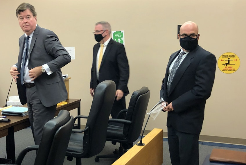 Elementary school principal Robin McGrath (right) prepares to leave the courtroom Tuesday with his lawyers Tom Johnson (left) and Ian Patey. He'll be back in provincial court in St. John's at the end of the month, when Judge David Orr will give his decision on an application made by prosecutor Shawn Patten.