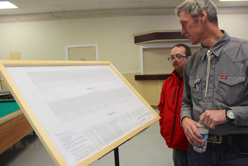 Haley Street program participants Camden MacDonald, left, and Richard MacDonald look over construction plans for Haley Street in North Sydney that was badly damaged last summer by arson. The non-profit's executive director said that after receiving $1-million from the province the construction of a new building could begin by April. ERIN POTTIE/CAPE BRETON POST