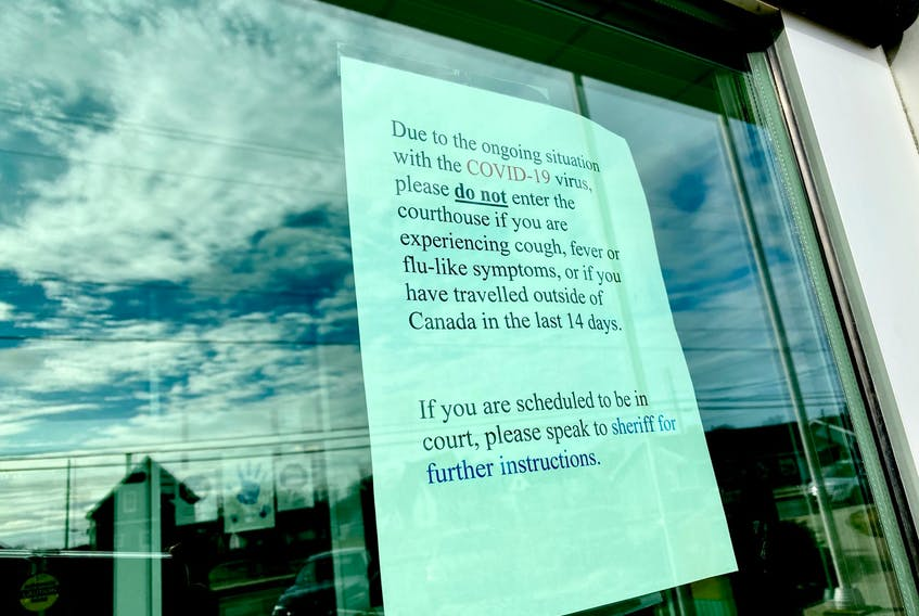 A message on the door of the Yarmouth Justice Centre telling people that if they're traveled outside of the country recently they are not allowed inside the courtroom. TINA COMEAU PHOTO