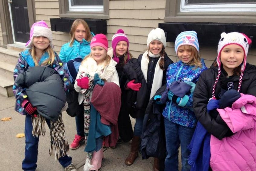 A group of young girls from Queens County joined their parents for a day of learning about what giving is all about. The girls along with their chaperones placed coats on telephone poles and lamp poles for anyone to take on Nov. 15.