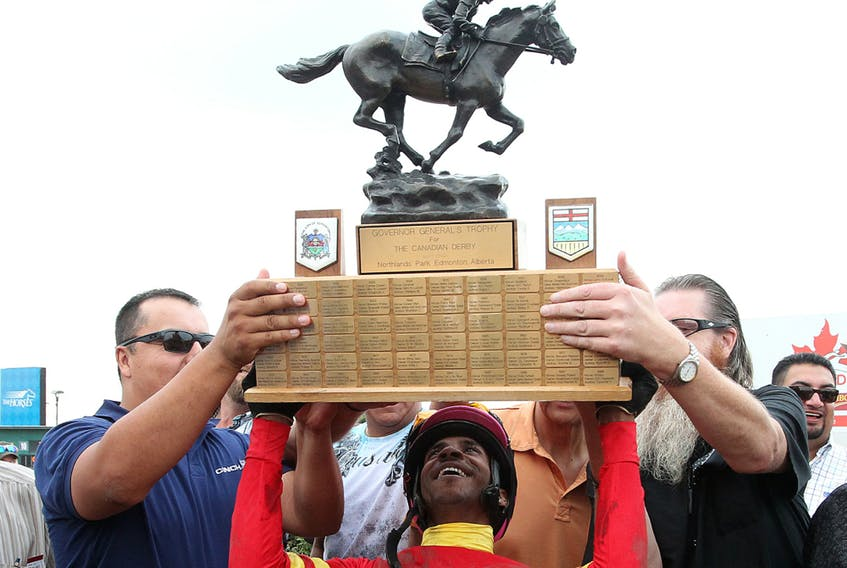 Jockey Rico Walcott holds up the Governor General's Trophy after winning the 85th Canadian Derby at Northlands Park on Aug. 16, 2014.