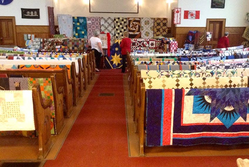 Visitors to a previous Sackville Quilters Guild's show check out the large variety of quilts on display.
