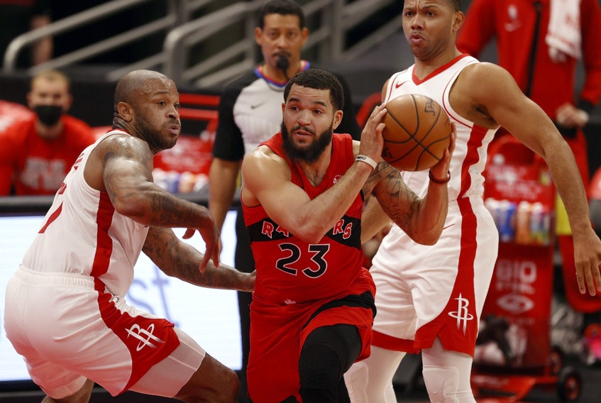 Toronto Raptors guard Fred VanVleet, centre, drives to the basket as Houston Rockets guard Eric Gordon and forward P.J. Tucker defend during the first half at Amalie Arena in Tampa, Fla., Feb. 26, 2021.