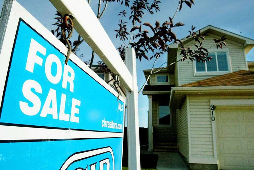 A for sale sign sits outside this home in the city of Coventry Hills in Alberta.
