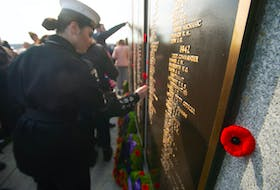 People place poppies on the Sailors' Memorial following the annual Remembrance Day ceremony at Point Pleasant Park on Monday.
