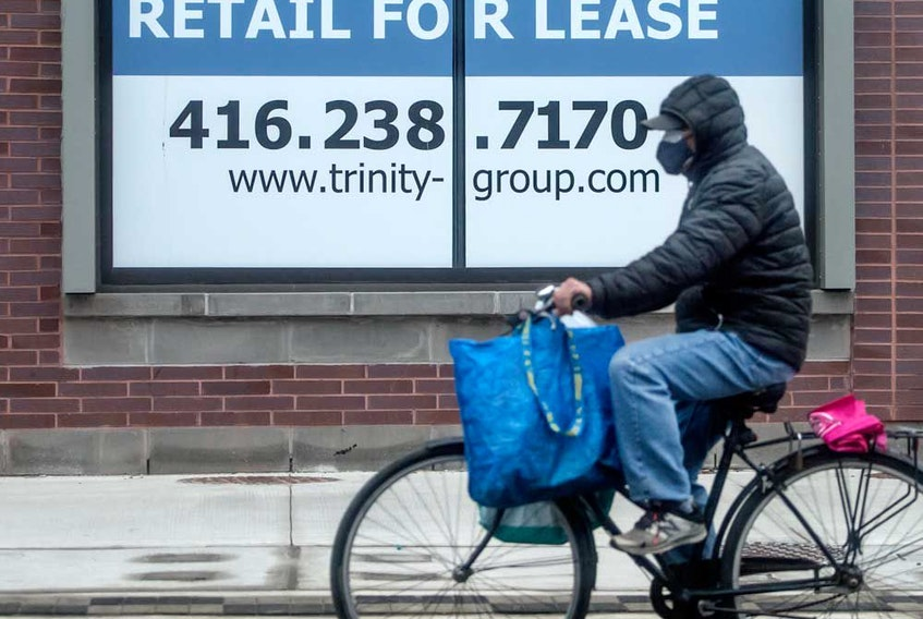 A cyclist rides past a Retail For Lease location on Queen Street East in Toronto during the COVID-19 pandemic.