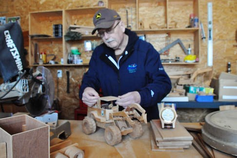 Bill Pike, a retired employee of the public works department with the Town of Stephenville, works at adding a roof to a wooden replica of a loader that he made in his garage workshop.