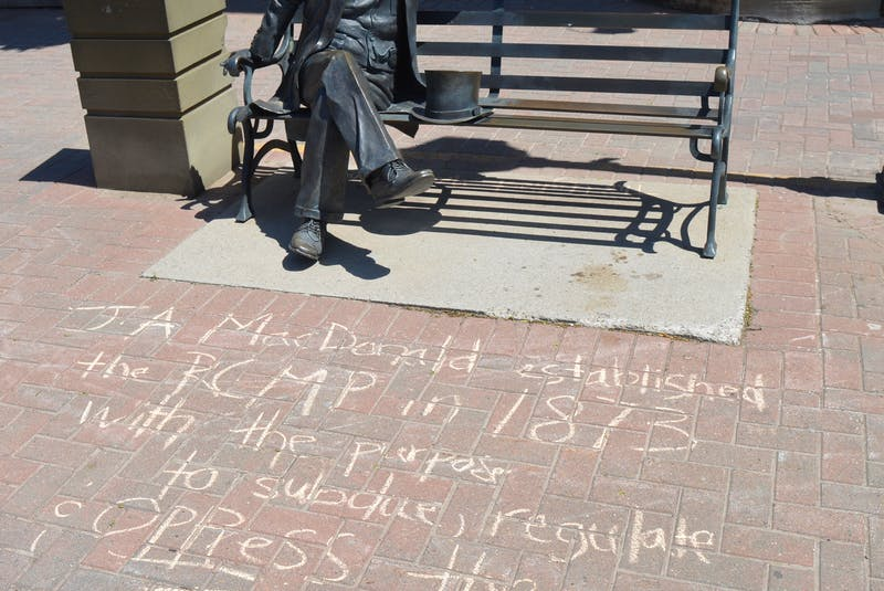 A message written in chalk at the bench statue of John A. Macdonald in Charlottetown references the first prime minister's role in trying to suppress the Indigenous population. - Dave Stewart