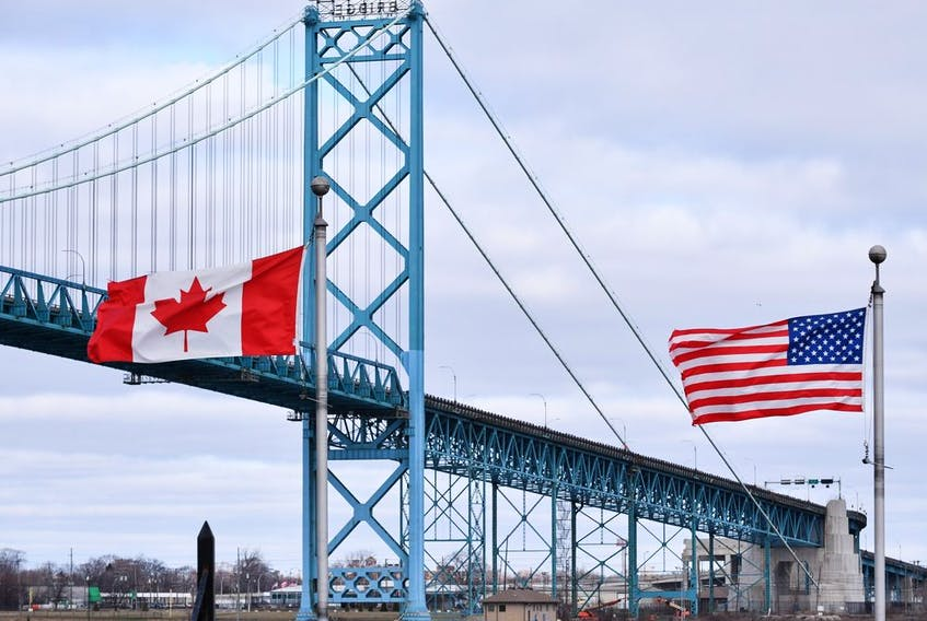Canadian and American flags fly near the Ambassador Bridge at the Canada-USA border crossing in Windsor, Ont. on Saturday, March 21, 2020.
