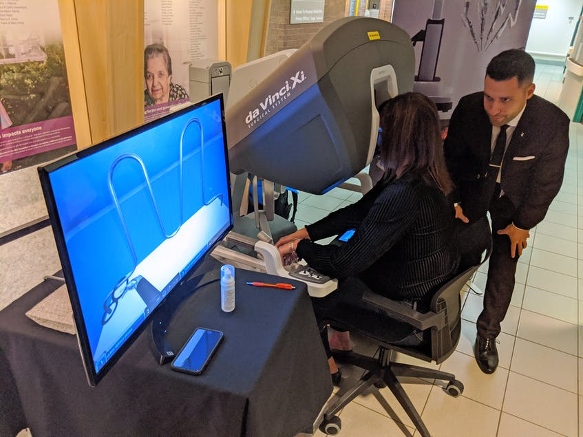 Lynn Malloy, a manager in perioperative services at the Halifax Infirmary, gets instructions on the robotic surgery demonstrator. - John McPhee