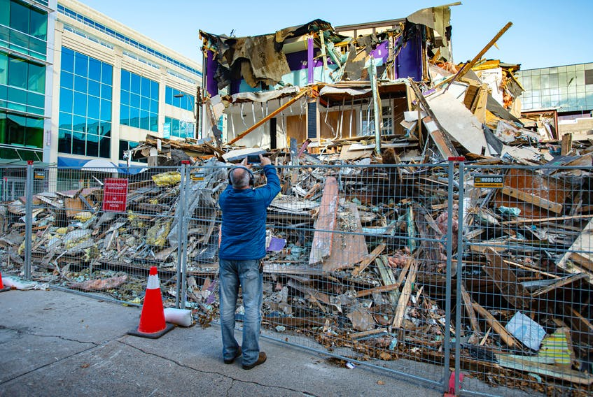A passerby takes a photo of the partially demolished Mills Brothers building near the intersection of Spring Garden Road and Birmingham Street on Nov. 22. Ryan Taplin - The Chronicle Herald