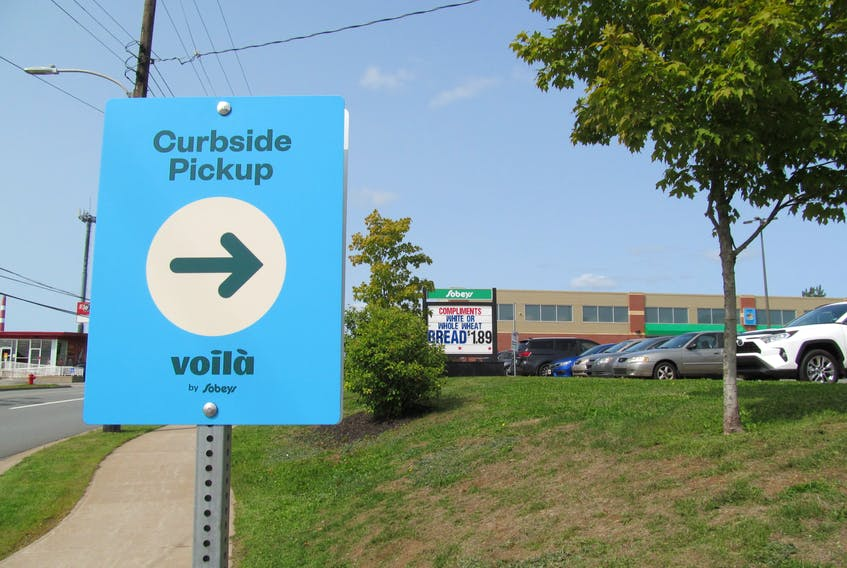 Empire Co. Ltd. is expanding its e-commerce offering with the launch of Voilà by Sobeys curbside pickup at three locations in Nova Scotia. A sign at the driveway of the Sobeys on Wyse Road in Dartmouth points the way for shoppers.