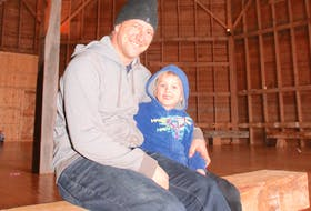 Beau Blois and his son Arlo take a break on one of the benches the family made while restoring the round barn.
