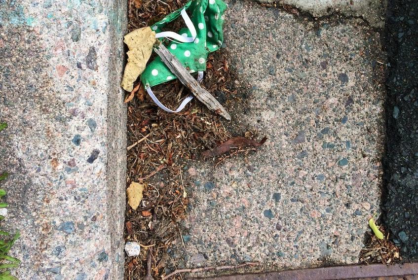 Abandoned mask near a city catch basin. RUSSELL WANGERSKY/SALTWIRE NETWORK