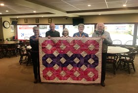 Sackville's Curl for Cancer committee members, l-r, Sheila Parker, Alan Johnson, Debbie Stewart, Greta Patterson and Wayne Harper hold up a quilt donated by the Sackville Quilter's Guilt, which will be raffled during the event to raise funds.