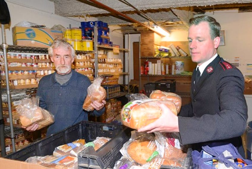 <span>Bill MacDonald and Capt. Jamie Locke sort through some bread that was donated at the Salvation Army in Charlottetown Wednesday. Locke and his wife Capt. Elaine Locke will soon be leaving the province after serving a three-year posting in the capital city.</span>