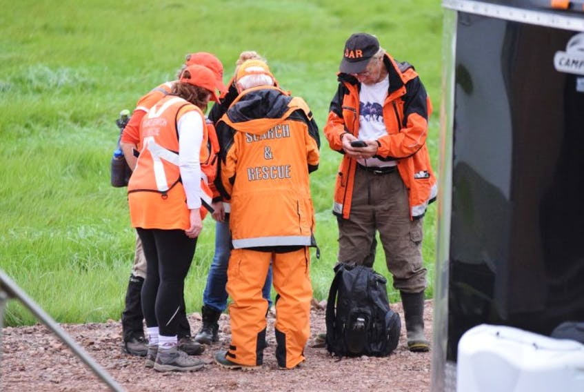 Search and rescue volunteers go over their search details before deploying in Lower Truro on Thursday. A total of eight search and rescue organizations from throughout the province are assisting the police from Halifax in an investigation into the murder of Taylor Samson