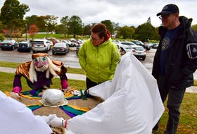 Carrie and Sean Mulrooney, visiting Charlottetown from Cape Breton, couldn't help but stop to take a look at these scarecrows holding a seance in front of Beaconsfield Historic House on Oct. 8.