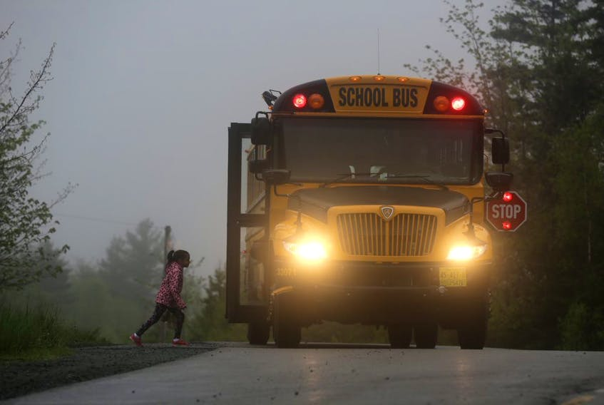 A young child boards a school bus on a dark, foggy morning near Lake Loon (Dartmouth) in this file photo.