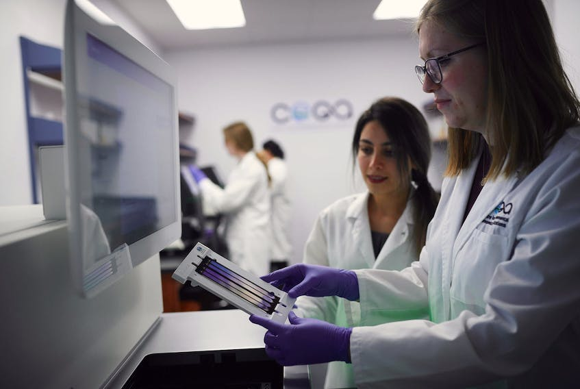 Hoda Rajabi (background) and Nicole Fahner (foreground) prepare to load a flow cell with environmental DNA into the NovaSeq 6000 DNA sequencing instrument at the eDNAtec lab in St. John's.