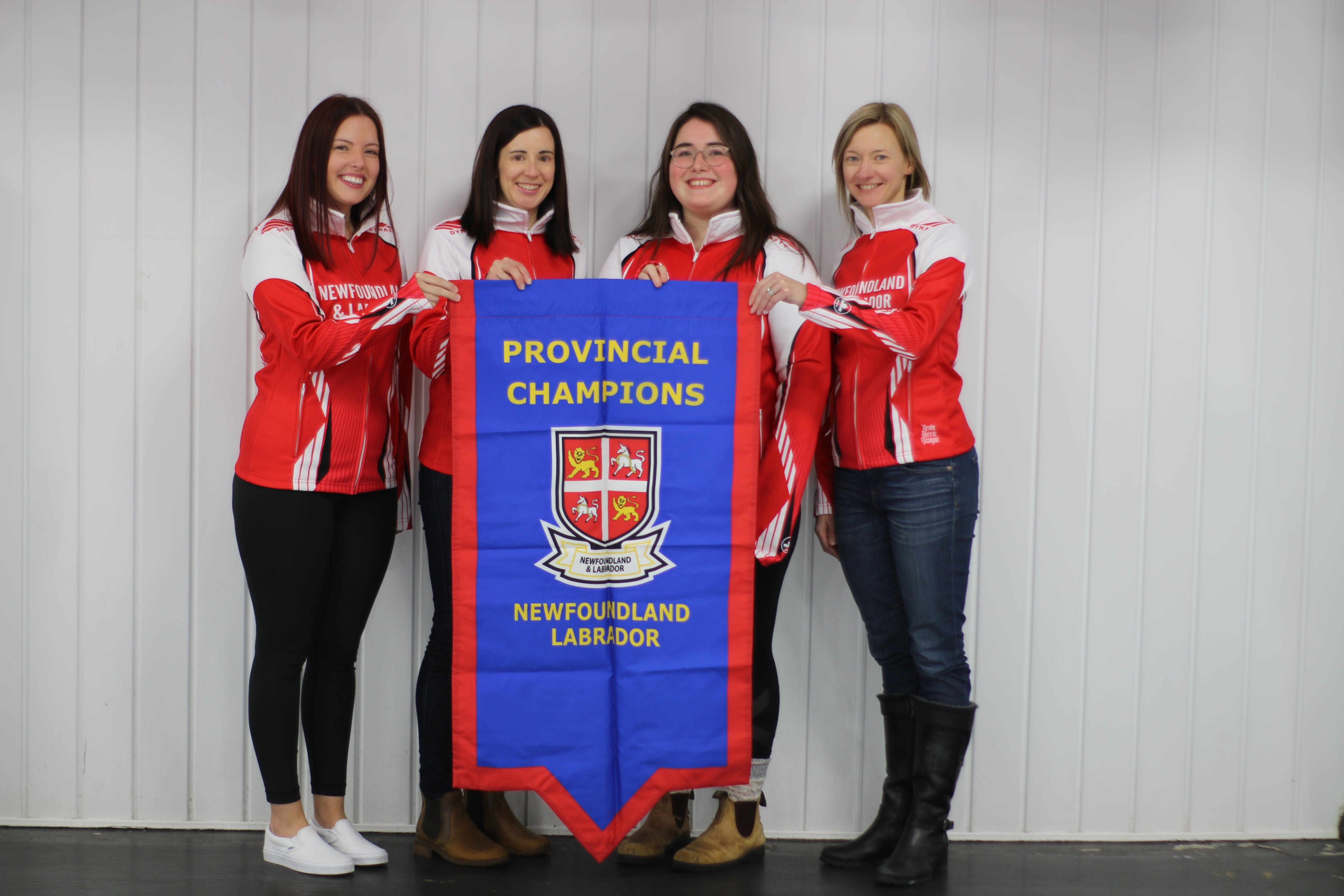 The members of the Sarah Hill-skipped rink hold up the championship banner after taking the 2021 Scotties Newfoundland and Labrador women's curling crown Saturday in St. John's by defeating Mackenzie Mitchell's team in a championship series. From left, Hill, Beth Hamilton, Laren Barron and Adrienne Mercer. — Contributed/Alex Phillips