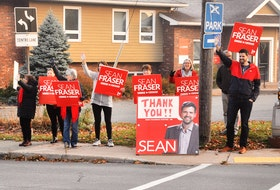 Sean Fraser waves to passersby the morning following the election.