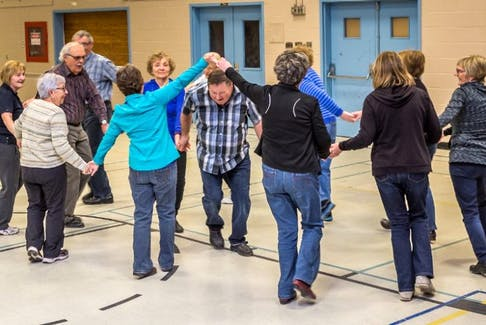 Dancers having a great time 'threading the needle' – the final set of the square dance.