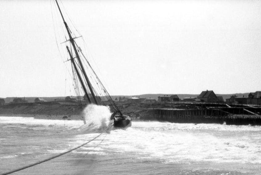 """A heavy northwest gale of wind proved to be the undoing of the 100 ton banking schooner """"Democracy"""" as she was attempting to leave her home port of Fortune in early May, 1933.  Just outside the harbour entrance she struck bottom and ran ashore becoming a total loss. The wooden flakes, which were used for drying the salt cod in that community, can be seen in the photo just to the right of the grounded vessel."""