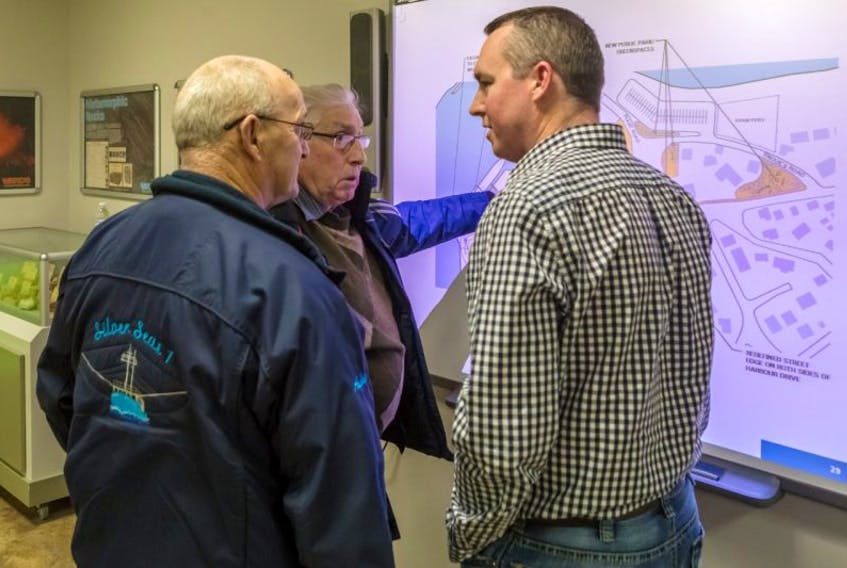 Fortune Port Corporation president Earl Rose (left), Aubrey Wells of the Fortune Harbour Authority (middle) and Fortune Town manager Corey Parsons look at some of the finer details of the development plan.