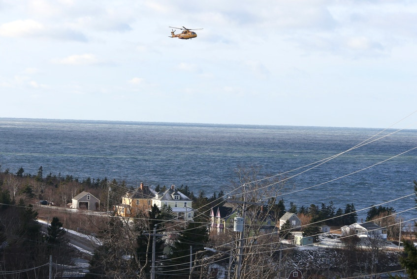 A Cormorant SnR helicopter searches Wednesday near Parker's Cove, N.S. for the five remaining crew members of the Chief William Saulis, which sank Tuesday. TIM KROCHAK PHOTO