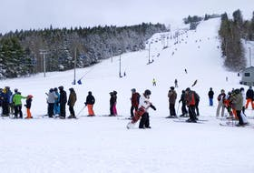 Skiers and snowboarders lined up for the lift at the base of the hill on opening day, Monday. People are required to wear masks except while skiing or snowboarding or on the lift and must remain two metres apart, except within their own bubbles.