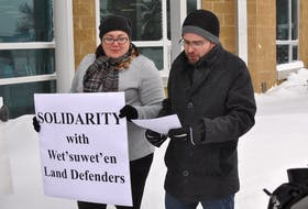 April Legge looks on as her partner Graham Downey-Sutton reads from a prepared speech during a demonstration in support of British Columbia's Wet'suwet'en First Nation outside Corner Brook City Hall on Friday. Diane Crocker/The Western Star