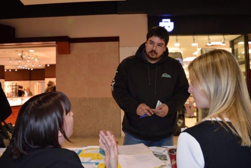 Nurse practitioner Hannah McKay, left, and pharmacist Ellen Penny speak with Eskasoni resident Julian Johnson about his options for quitting smoking. A smoking cessation booth will be set up in the Mayflower Mall over the next six Saturdays providing prescriptions and reading material on what they can do to kick the habit.