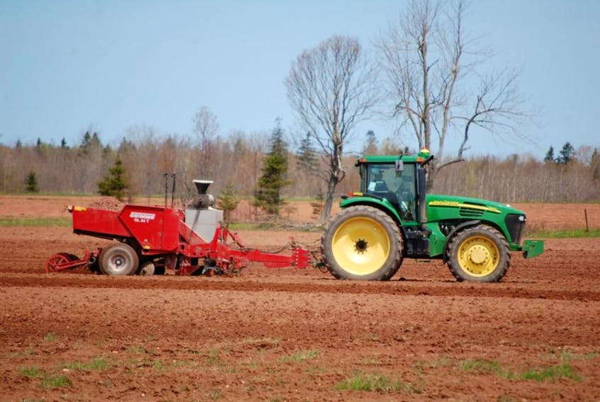 <p>A wet spot is avoided as a tractor and planter put in a crop of potatoes in a field off the Piusville Road Thursday morning. A cool, wet spring has left many farmers behind schedule but they have been making headway in the past week.</p>