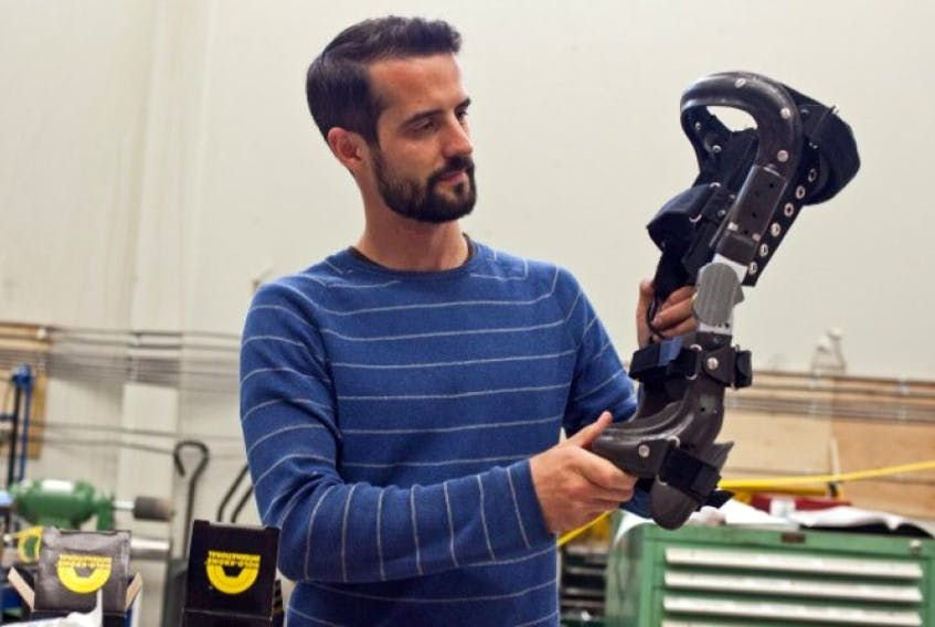 Chris Cowper-Smith, CEO of Spring Loaded Technology Inc. holds a knee brace in the production area of the firms Burnside location.