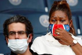 Fans wear protective face masks at a soccer game at Parc des Princes, Paris, on Fri. July 17, 2020.