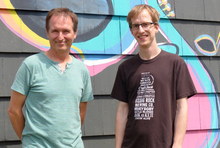 Darcy Rhyno (left) and Alex Buchanan stand in front of the mural at Buchanan's HarbourTone Productions in Shelburne.
