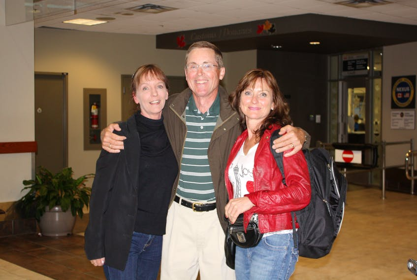 Gordon McMillan is all smiles as he poses with his half-sister Mary Morris, left, and his wife, Lyn, just moments after Morris stepped off a plane in Halifax and they met in person for the first time.