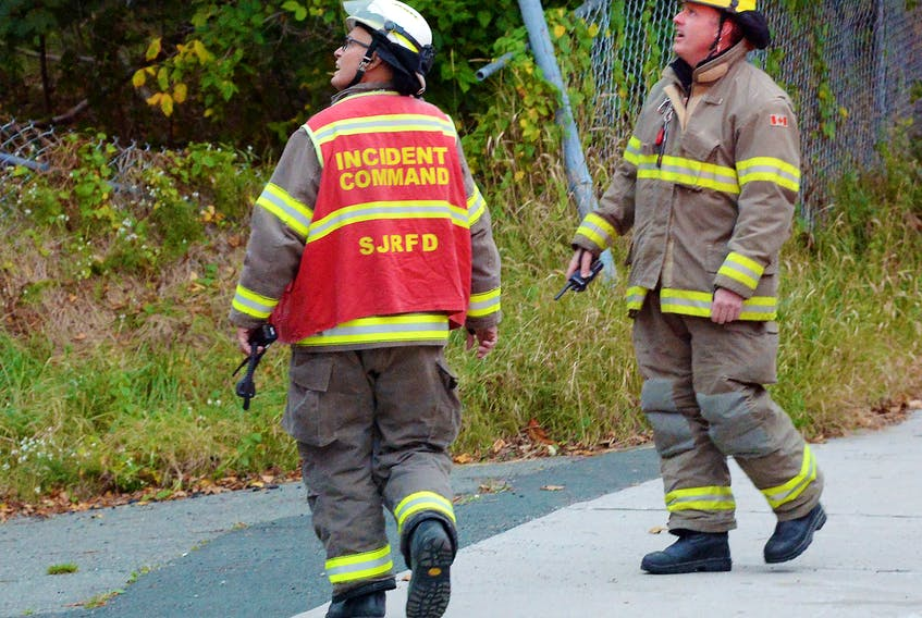 Members of the St. John's Regional Fire Department use portable radios at the scene of a fire at the old West End fire station in October 2020. Telegram File Photo