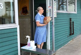 A Ches's Famous Fish and Chips employee leaves an order outside the Freshwater Road location for contactless pickup. — ANDREW ROBINSON/THE TELEGRAM