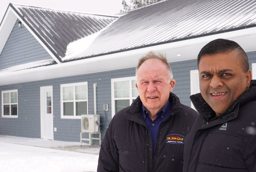 Ajay Mathew Punnapadam, right, and Doug MacKenzie stand outside some of the finished staff housing units for Dr. John M. Gillis Memorial Lodge in Belfast.
