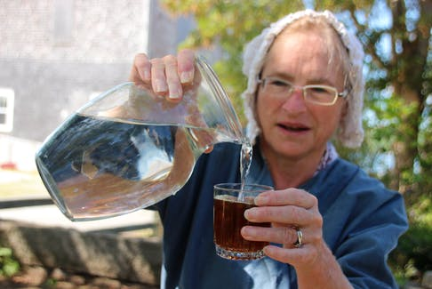 Greta Mossman, senior interpreter, adds water to switchel at the Ross-Thomson House and Store Museum in Shelburne, N.S. Switchel is the 18th-century version of a sports drink.